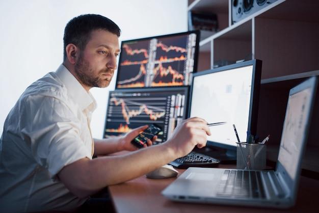 El corredor de bolsa en camisa está trabajando en una sala de monitoreo con pantallas. gráfico de la bolsa de comercio forex finanzas. empresarios que negocian acciones en línea