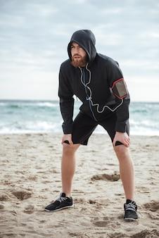 Corredor cansado de longitud completa en la playa mirando a otro lado
