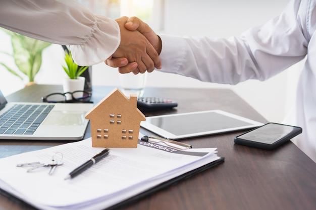El corredor de la casa residencial le da la mano al cliente después de un acuerdo exitoso y la firma del contrato de la casa, el concepto inmobiliario