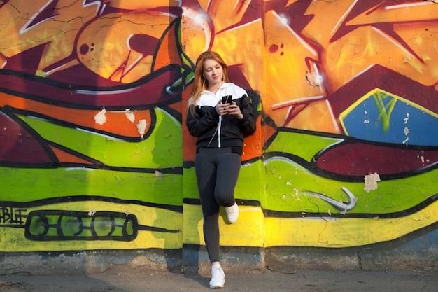 Corredor chica descansando con teléfono móvil contra la pared de graffiti brillante