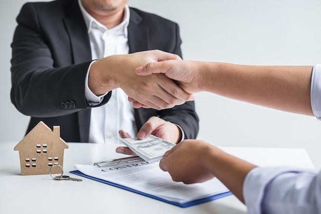 Corredor y cliente dándose la mano después de firmar el contrato de alquiler