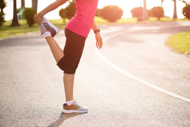 Corredor estirando las piernas antes de correr en el parque. concepto de ejercicio al aire libre.