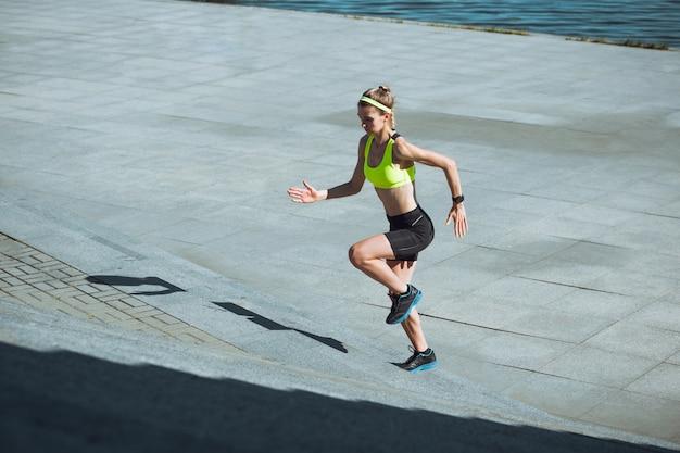 Corredor femenino, atleta entrenando al aire libre en el día soleado de verano.