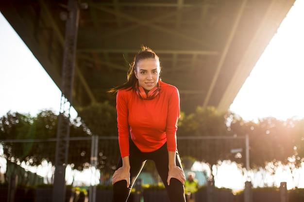 Corredor femenino atractivo tomando descanso después de correr al aire libre