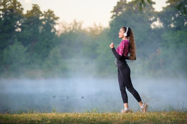 Corredor femenino de pie cerca del lago con auriculares en