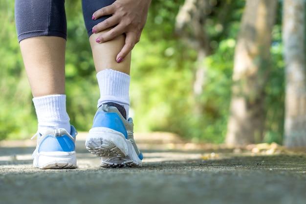 Corredor femenino que tiene dolor en las piernas por el ejercicio