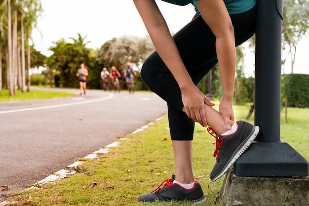 Corredor de fitness mujer siente dolor en la pierna del tobillo