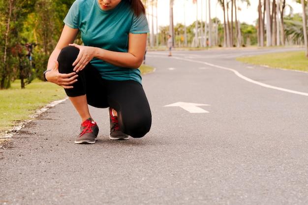 Corredor de fitness mujer siente dolor en la rodilla