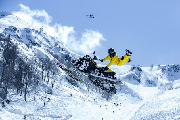 Corredor en un gato de nieve en vuelo, salta y despega en un trampolín contra las montañas nevadas