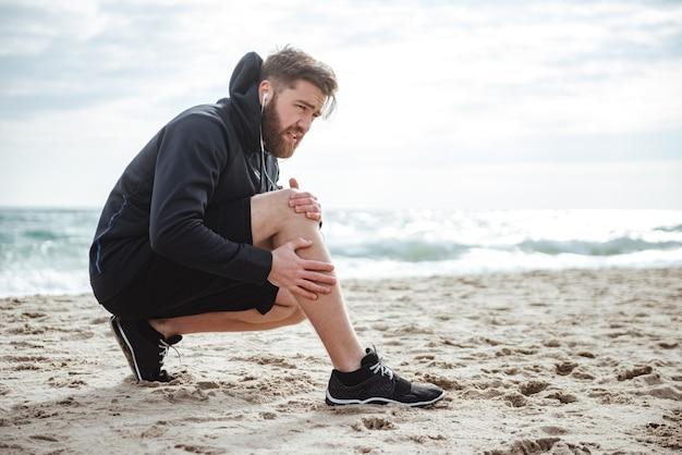 Corredor herido en vista lateral de la playa