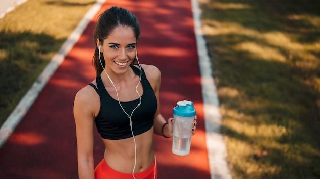 El corredor hermoso de la muchacha que escucha la motivación de la música con los auriculares que se preparan para el entrenamiento cardiovascular se ejecuta al aire libre.