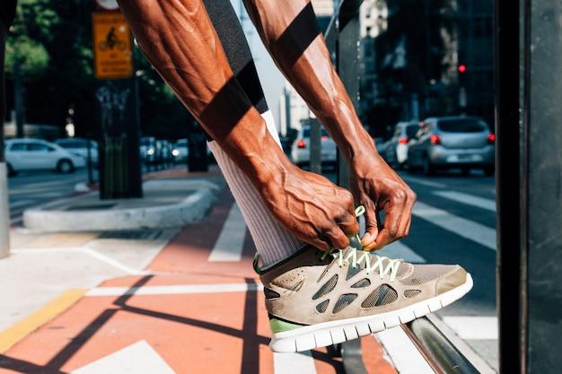 Corredor hombre atar cordones de zapatos para entrenamiento deportivo en carretera.