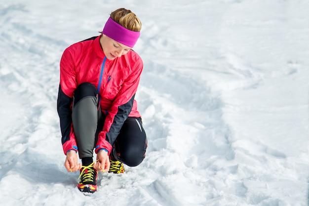 Corredor de invierno preparándose corriendo atando cordones de los zapatos.
