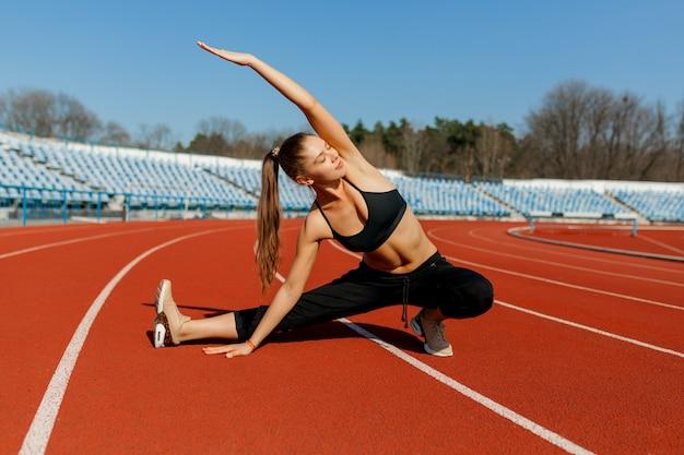 Corredor joven de la mujer de la aptitud calienta antes de correr en pista. ejercicios matinales en verano.