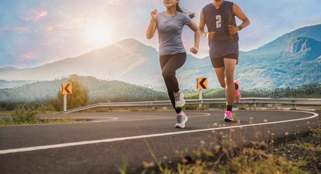Corredor de la joven pareja corriendo en la carretera en el parque de la ciudad con montañas al fondo. concepto de funcionamiento saludable.