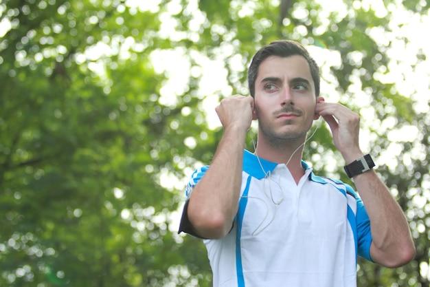 Corredor masculino deportivo ajustando sus auriculares durante el jogging con espacio de copia