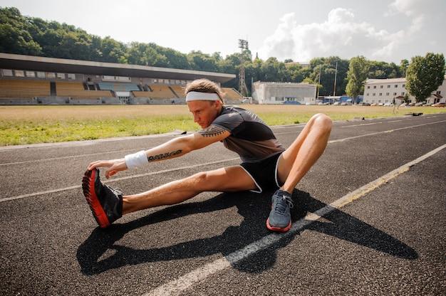 Corredor masculino estiramiento antes del entrenamiento