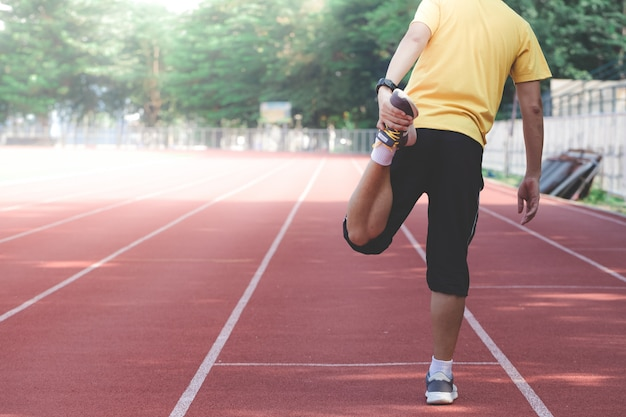 Corredor masculino estirando piernas y pies y preparándose para correr al aire libre.