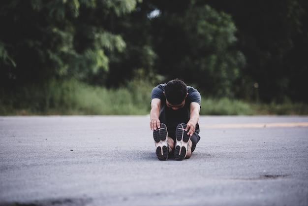 Corredor masculino haciendo ejercicios de estiramiento, preparándose para el entrenamiento