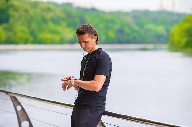Corredor mirando reloj inteligente monitor de ritmo cardíaco que tiene descanso mientras se ejecuta