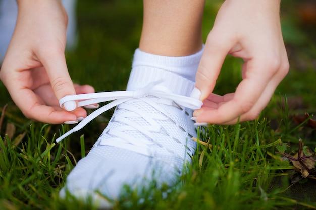Corredor de mujer apriete el cordón del zapato. pies de la mujer del corredor que se ejecutan en primer plano de la carretera en el zapato.