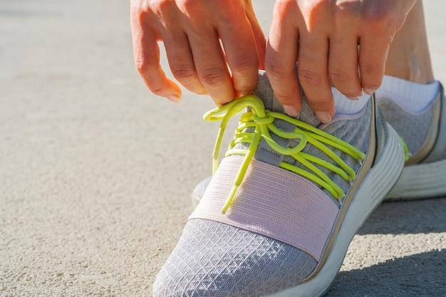Corredor de mujer atando sus cordones de zapatos preparándose para una carrera matutina