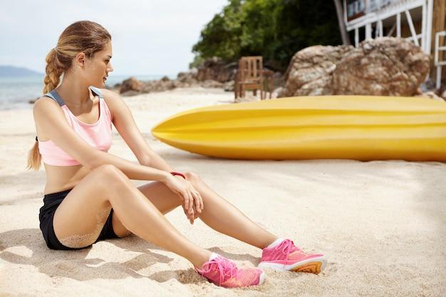 Corredor de mujer cansada en zapatillas rosa relajante después de un entrenamiento activo, sentado en la playa cerca del barco amarillo.