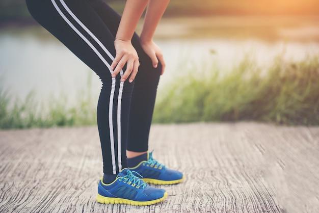Corredor de mujer de fitness cansado tomando un descanso después de correr rápido