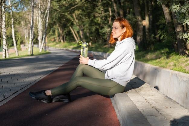 Corredor de mujer de jengibre delgado en ropa deportiva sentado en el parque de agua potable estilo de vida saludable