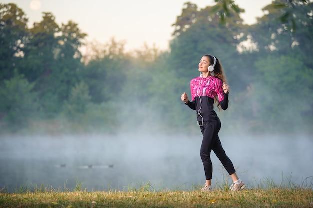 Corredor de la mujer en la mañana brumosa de pie cerca del lago