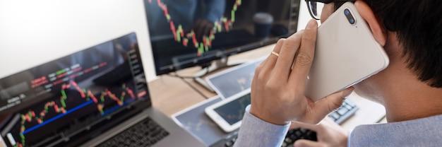 Corredor de negocios analizando informes y gráficos de datos financieros