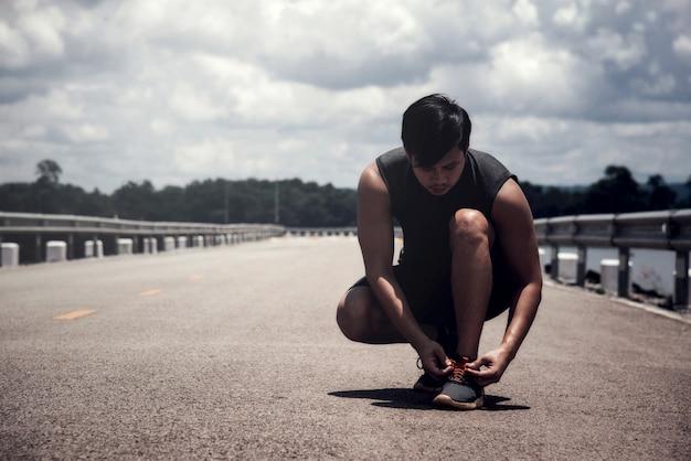 El corredor que ata los zapatos para correr.