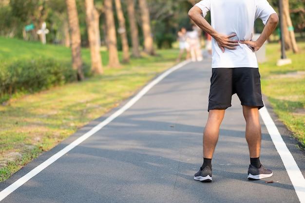 Corredor que tiene dolor de espalda y problema después de correr y hacer ejercicio fuera de la mañana