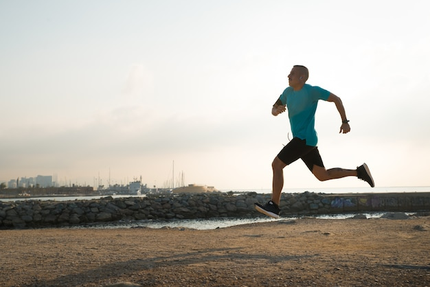 Corredor rápido entrenamiento solo en la playa