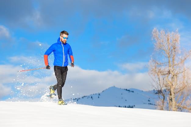 Corredor con raquetas de nieve cuesta abajo en un día soleado