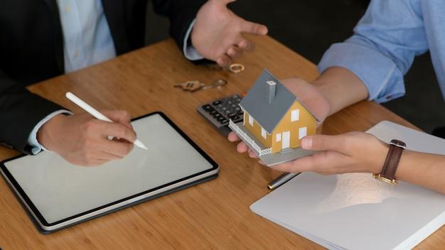 El corredor recomienda paquetes de seguros inmobiliarios a los clientes.