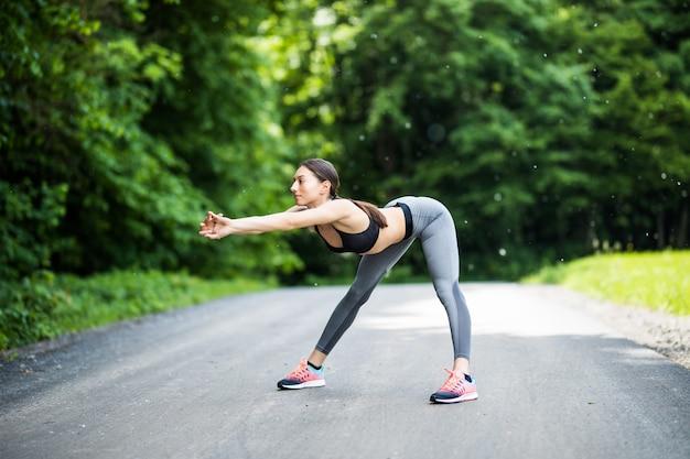 Corredor de sexo femenino joven que estira los brazos antes de correr.