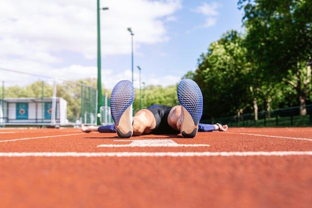 Corredor tirado en el suelo y cansado en la cancha de atletismo.