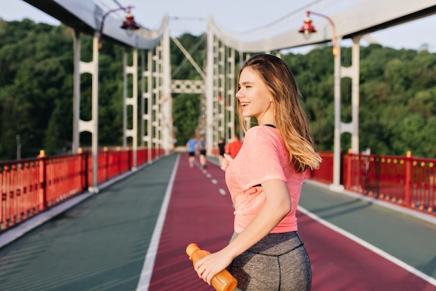 Corredora dichosa disfrutando de buenos días. retrato al aire libre de linda chica blanca corriendo en el estadio.