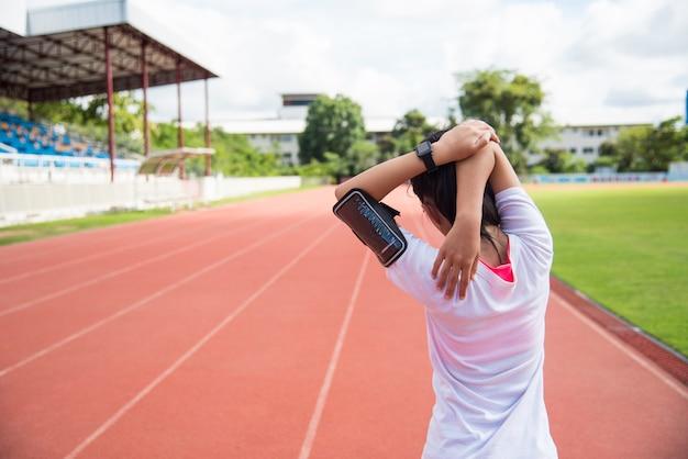 La corredora femenina se está calentando antes de trotar en el campo.