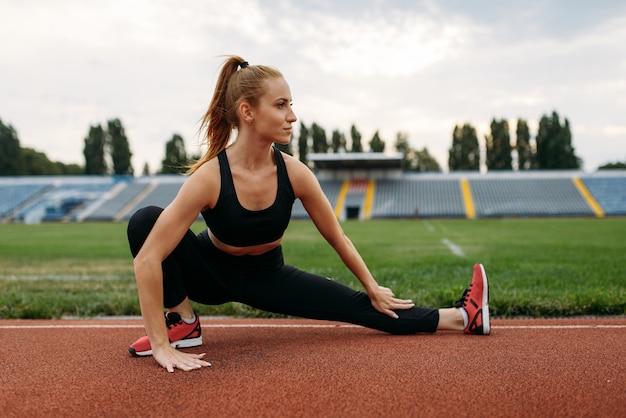 Corredoras en ropa deportiva, entrenamiento en el estadio. mujer haciendo ejercicio de estiramiento antes de correr en la arena al aire libre