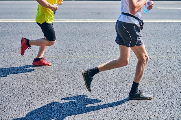 Corredores de maratón en el camino de la ciudad, evento deportivo, ropa deportiva en el camino de la ciudad