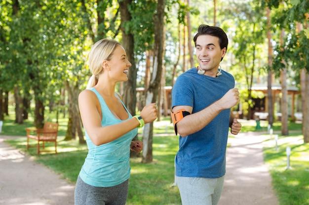 Corredores matutinos. bonita pareja feliz mirándose mientras corren juntos por la mañana