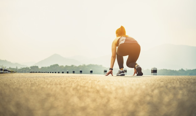 Los corredores de mujer en las zapatillas de carretera están preparados para abandonar el punto de partida.