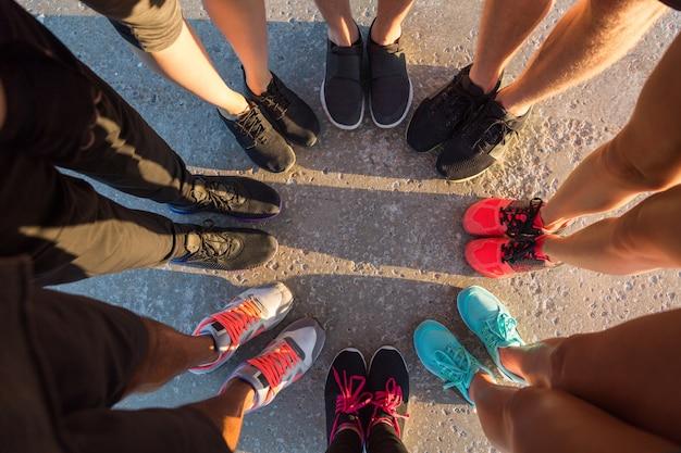 Corredores de pie en un grupo con los pies juntos