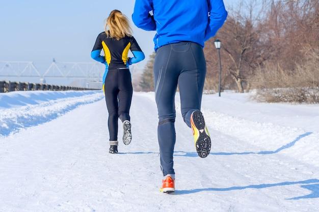 Corredores. piernas, vista posterior. jóvenes parejas corriendo. sport hombre y mujer trotar en el parque de invierno