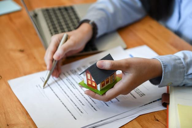 Corredores de ventas de viviendas tienen pluma y casa modelo en mano.