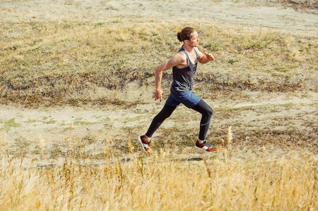 Correr deporte. hombre corredor corriendo al aire libre en la naturaleza escénica. ajuste musculoso atleta masculino sendero de entrenamiento para correr maratón.
