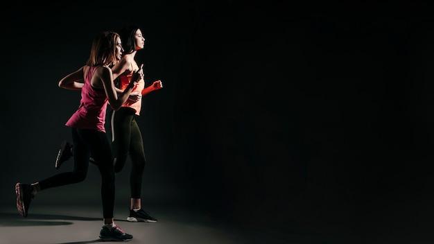 Correr mujeres deportivas en la oscuridad