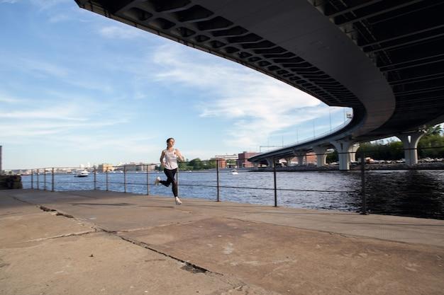 Corriendo por el paseo marítimo de la ciudad al atardecer